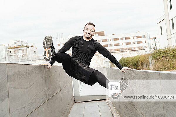 Playful sportsman smiling while swinging on rooftop retaining wall