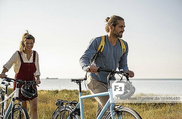 Smiling man and woman with bicycles walking against clear sky
