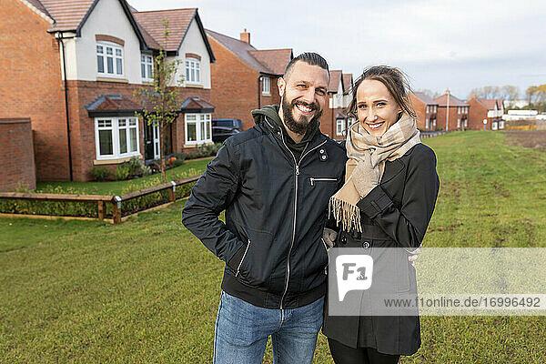 Glückliches Paar  das gemeinsam vor neu gebauten Häusern steht