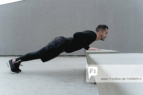 Male athlete doing push-up while exercising against wall