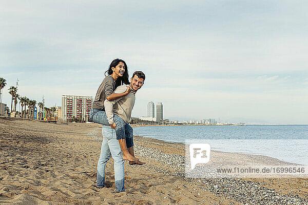 Junger Mann  der eine Frau gegen den Himmel am Strand huckepack nimmt Junger Mann, der eine Frau gegen den Himmel am Strand huckepack nimmt