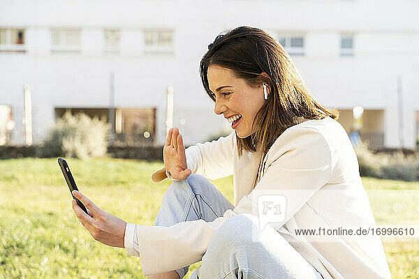 Happy female entrepreneur doing video call through smart phone while sitting on grass in garden