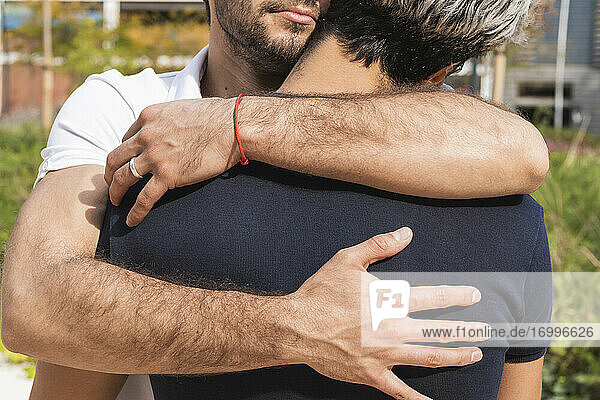 Man embracing partner in park during sunny day