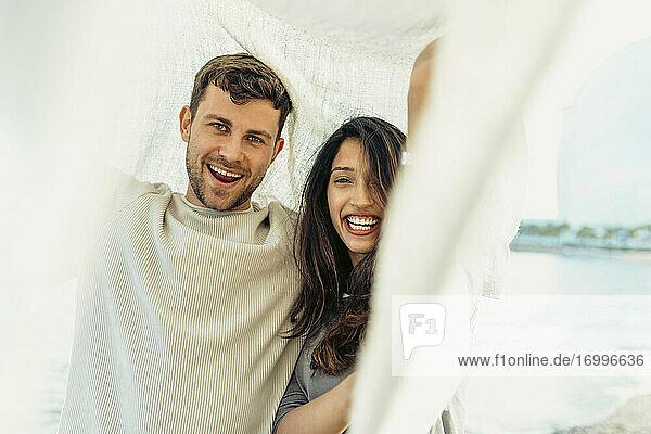 Freundin und Freund lachen  während sie unter einem Schal stehen Freundin und Freund lachen, während sie unter einem Schal stehen
