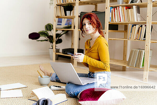 Young woman with laptop on lap using mobile phone while sitting at home