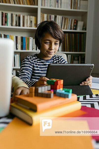 Lächelnder Junge mit digitalem Tablet am Tisch Lächelnder Junge mit digitalem Tablet am Tisch