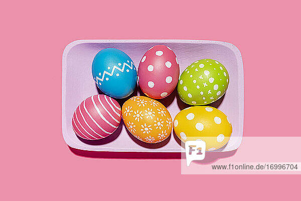 Handmade painted Easter eggs in purple tray on pink background