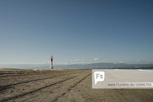 Clear sky over empty Platja del Fangar beach with Far del Fangar lighthouse in background