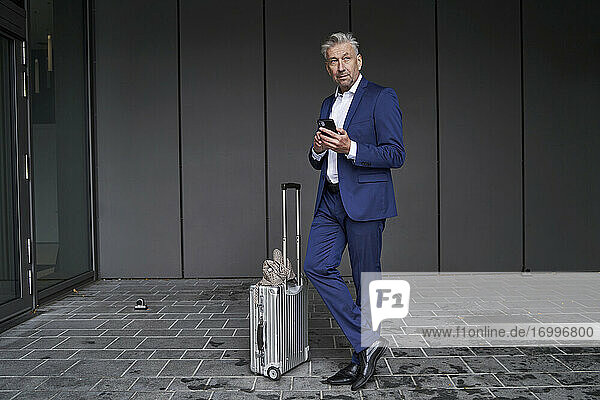Businessman using mobile phone while standing with luggage on footpath