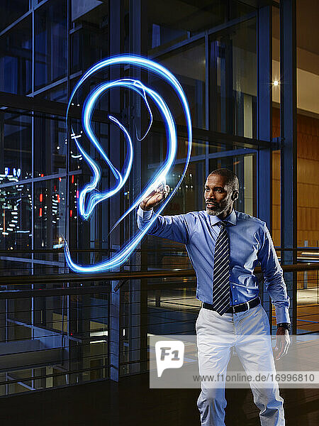 Mature male specialist light painting ear in laboratory at hospital