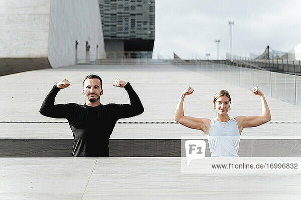 Athletes showing muscles while standing by retaining wall