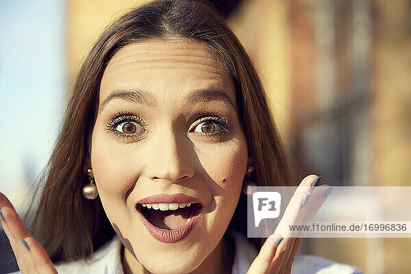 Close-up of businesswoman with surprised facial expression standing outdoors