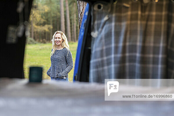 Smiling woman seen from door of camper van at Cannock Chase