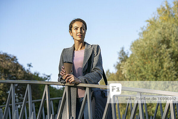 Businesswoman leaning on railing while standing over footbridge during autumn