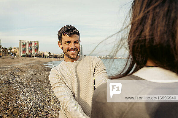 Junger Mann lächelt  während er eine Frau betrachtet  die gegen den Himmel steht Junger Mann lächelt, während er eine Frau betrachtet, die gegen den Himmel steht