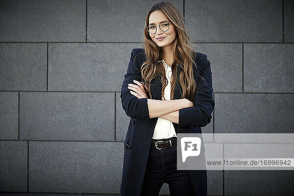 Young business professional standing with arms crossed against brick wall