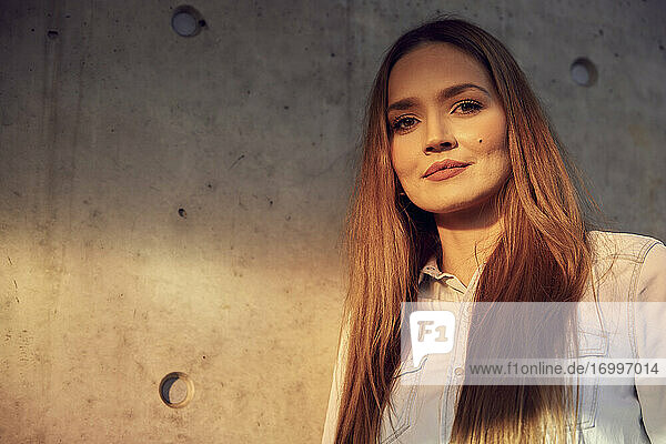 Young beautiful businesswoman standing against wall