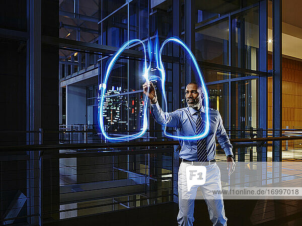 Male pulmonologist light painting lung in laboratory at hospital