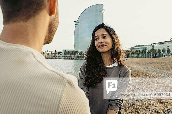 Lächelnde Frau  die einen Mann ansieht  während sie vor einem klaren Himmel steht Lächelnde Frau, die einen Mann ansieht, während sie vor einem klaren Himmel steht