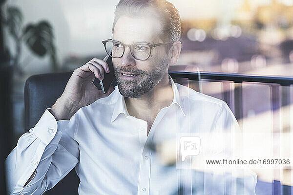Lächelnder Geschäftsmann  der im Büro sitzt und mit seinem Handy telefoniert Lächelnder Geschäftsmann, der im Büro sitzt und mit seinem Handy telefoniert