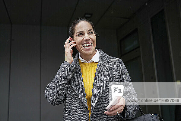 Businesswoman with mobile phone laughing while standing outdoors
