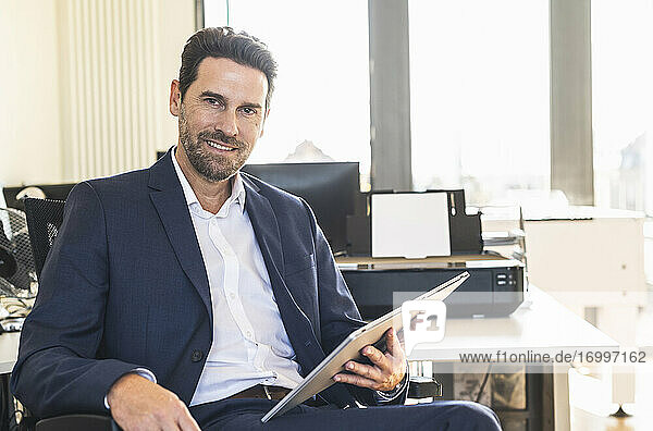 Businessman smiling while using digital tablet sitting at office