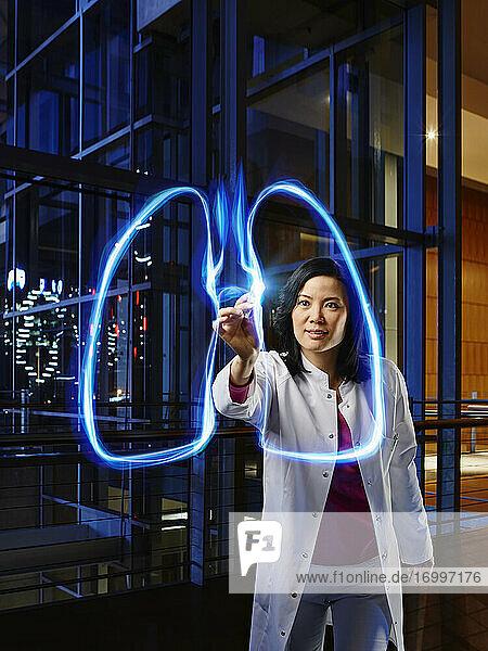 Ältere Pulmologin  die die Lunge im Labor des Krankenhauses mit Licht malt Ältere Pulmologin, die die Lunge im Labor des Krankenhauses mit Licht malt