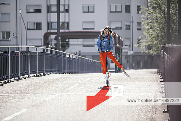 Young woman ridingpush Scooteralong empty street