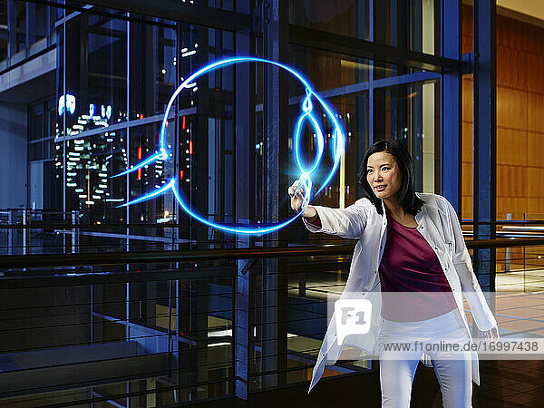 Mature female ophthalmologist light painting in laboratory at hospital
