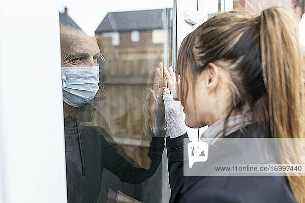 Young woman looking at boyfriend through window glass during coronavirus outbreak