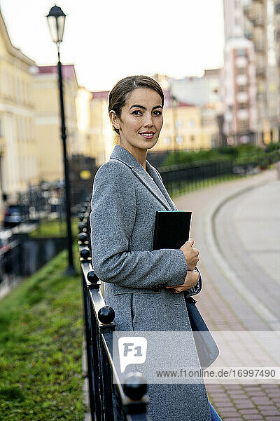Female entrepreneur holding diary while leaning on railing in city during autumn