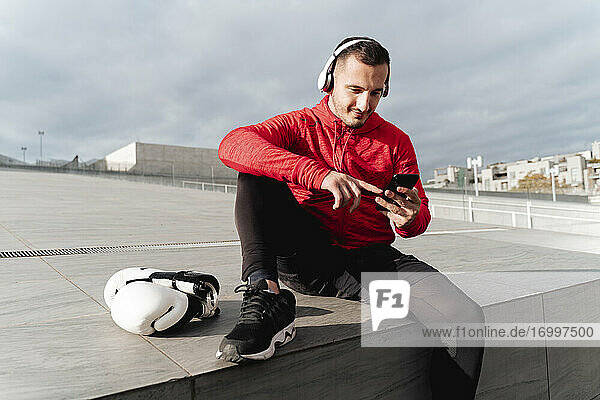 Sportsman wearing headphones using mobile phone while sitting by boxing gloves outdoors