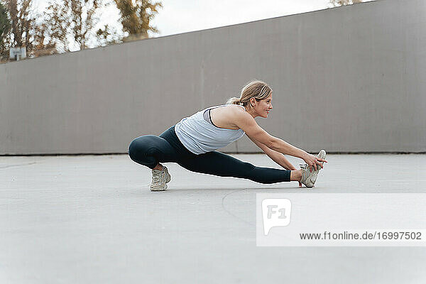 Smiling woman stretching legs while exercising against wall
