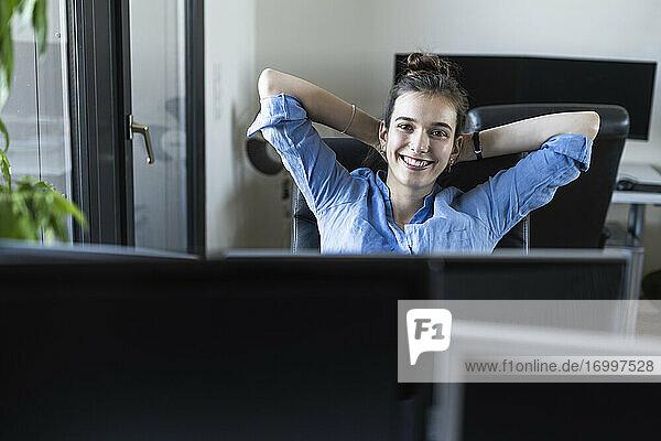 Lächelnde Geschäftsfrau sitzt mit den Händen hinter dem Kopf auf einem Stuhl im Büro Lächelnde Geschäftsfrau sitzt mit den Händen hinter dem Kopf auf einem Stuhl im Büro