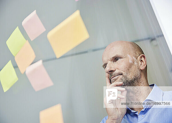 Thoughtful businessman reading adhesive note while standing by glass wall