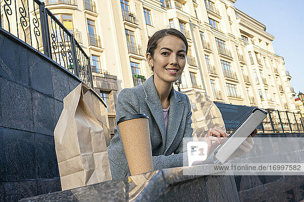 Smiling business holding digital tablet while leaning on railing in city during autumn