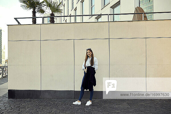 Young entrepreneur holding blazer while standing on footpath