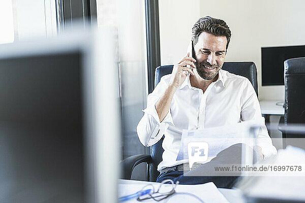 Geschäftsmann  der auf Papier schaut  während er im Büro sitzt und mit seinem Handy spricht Geschäftsmann, der auf Papier schaut, während er im Büro sitzt und mit seinem Handy spricht