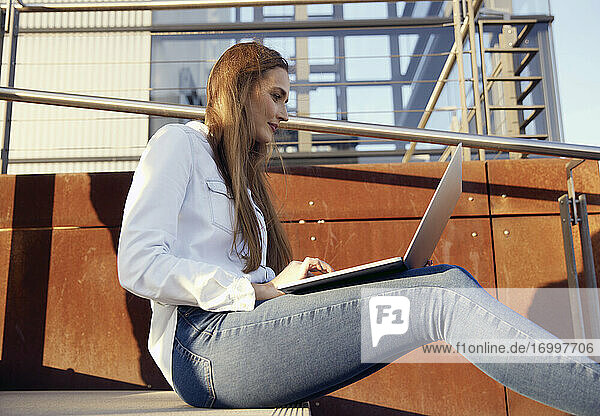 Young businesswoman working on laptop while sitting on steps