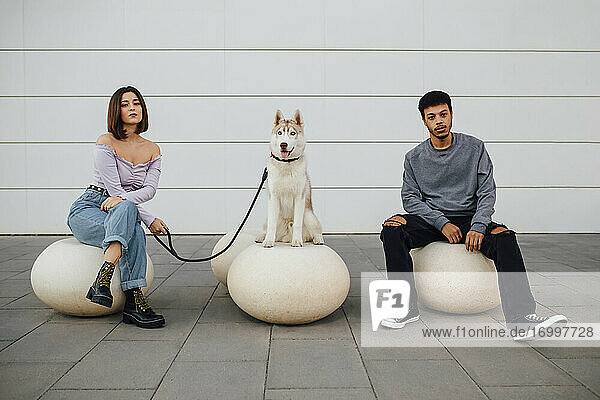 Boyfriend and girlfriend sitting by dog with social distance on white concrete ball against wall