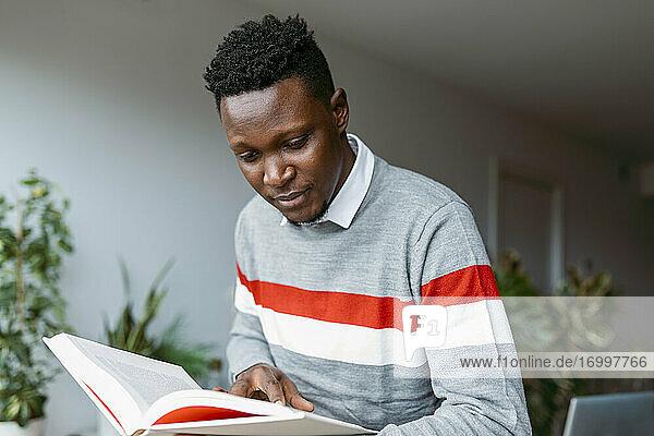 Männlicher Freiberufler bei der Recherche  während er zu Hause ein Buch liest Männlicher Freiberufler bei der Recherche, während er zu Hause ein Buch liest