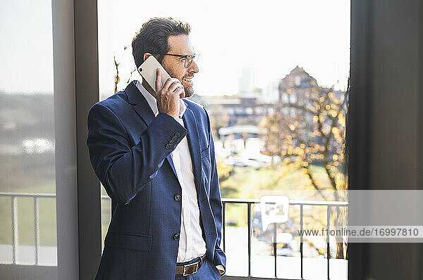 Mature businessman talking on mobile phone while standing by balcony at office