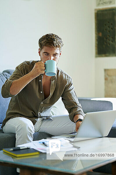 Businessman drinking coffee while working on laptop at home