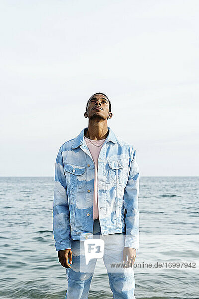 Young man wearing clouds denim suit looking up while standing against sea