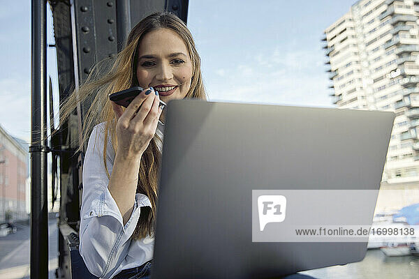 Smiling businesswoman talking on mobile phone while sitting outdoors