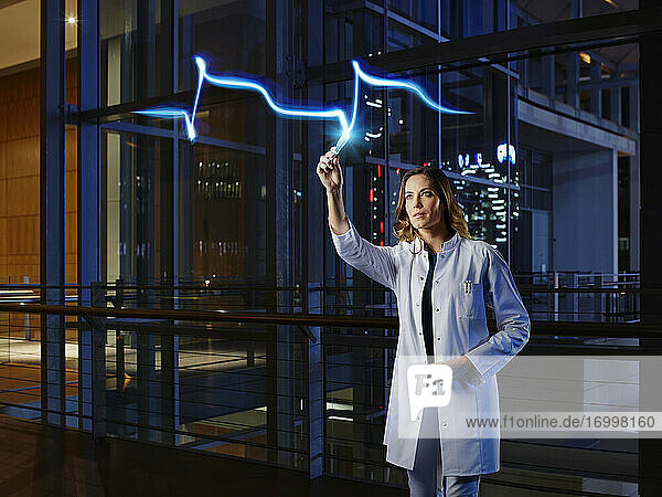 Female doctor light painting heart attack in laboratory at hospital