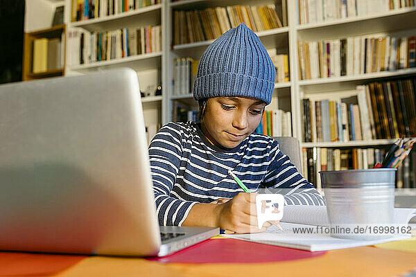 Lächelnder Junge mit Strickmütze  der in ein Buch schreibt  während er zu Hause sitzt Lächelnder Junge mit Strickmütze, der in ein Buch schreibt, während er zu Hause sitzt