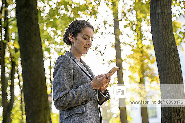 Businesswoman text messaging on smart phone while standing in park during autumn