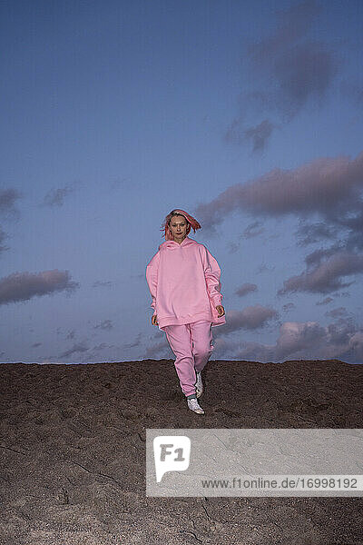 Portrait of young woman with pink hair wearing pink hooded shirt on beach at sunset