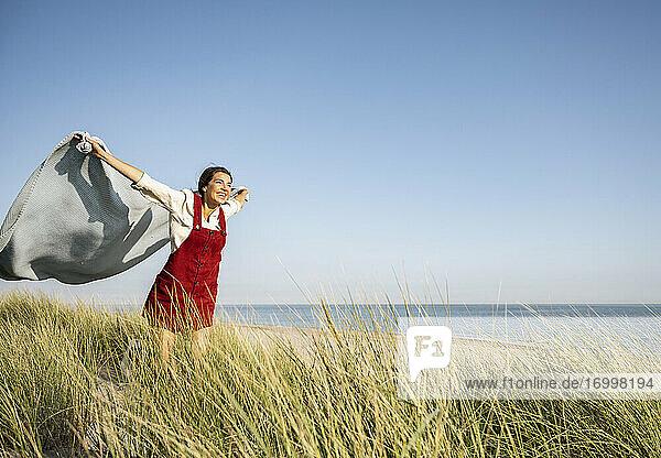 Junge Frau mit ausgestreckten Armen  die einen Schal hält  während sie am Strand steht Junge Frau mit ausgestreckten Armen, die einen Schal hält, während sie am Strand steht